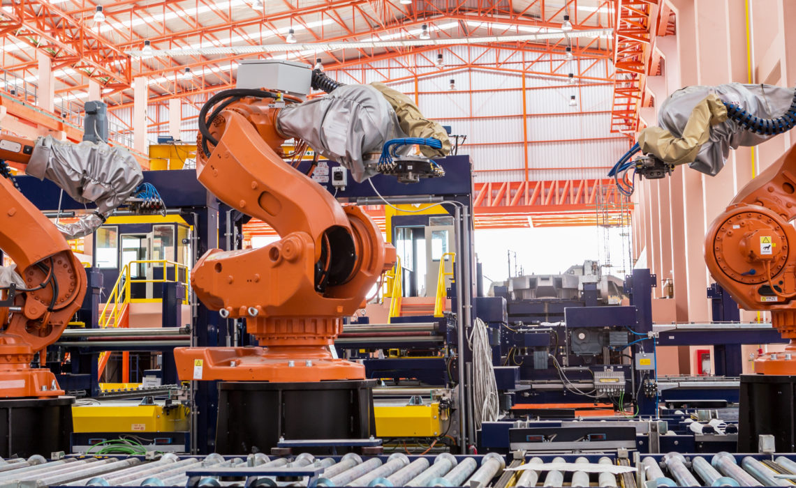 Industrial welding robots in production line manufacturer factory.