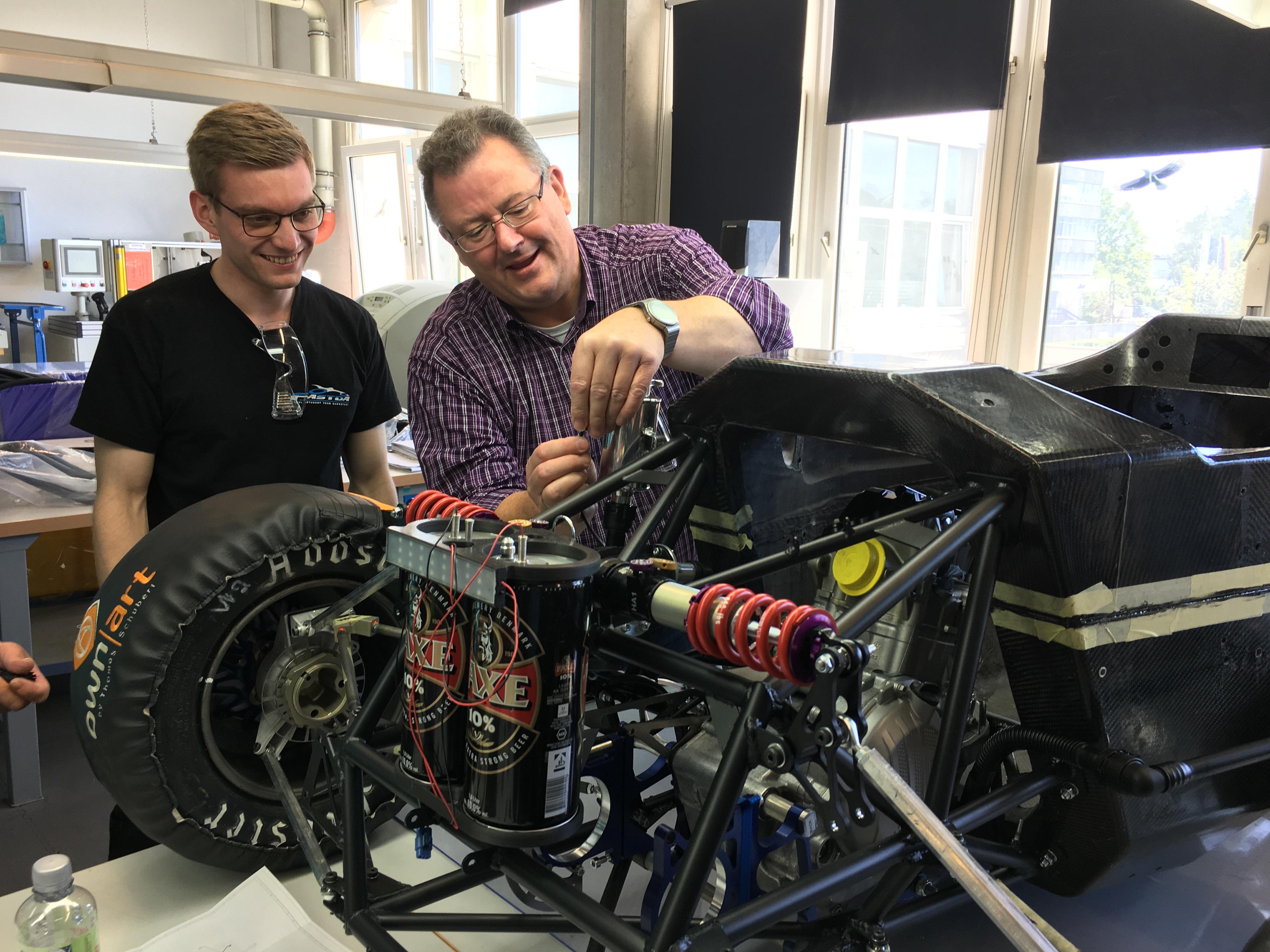 Lukas Koenen und Director Forschung und Entwicklung Stephan Mann von der NORMA Group beim Einbau des Kühlsystems in den F19