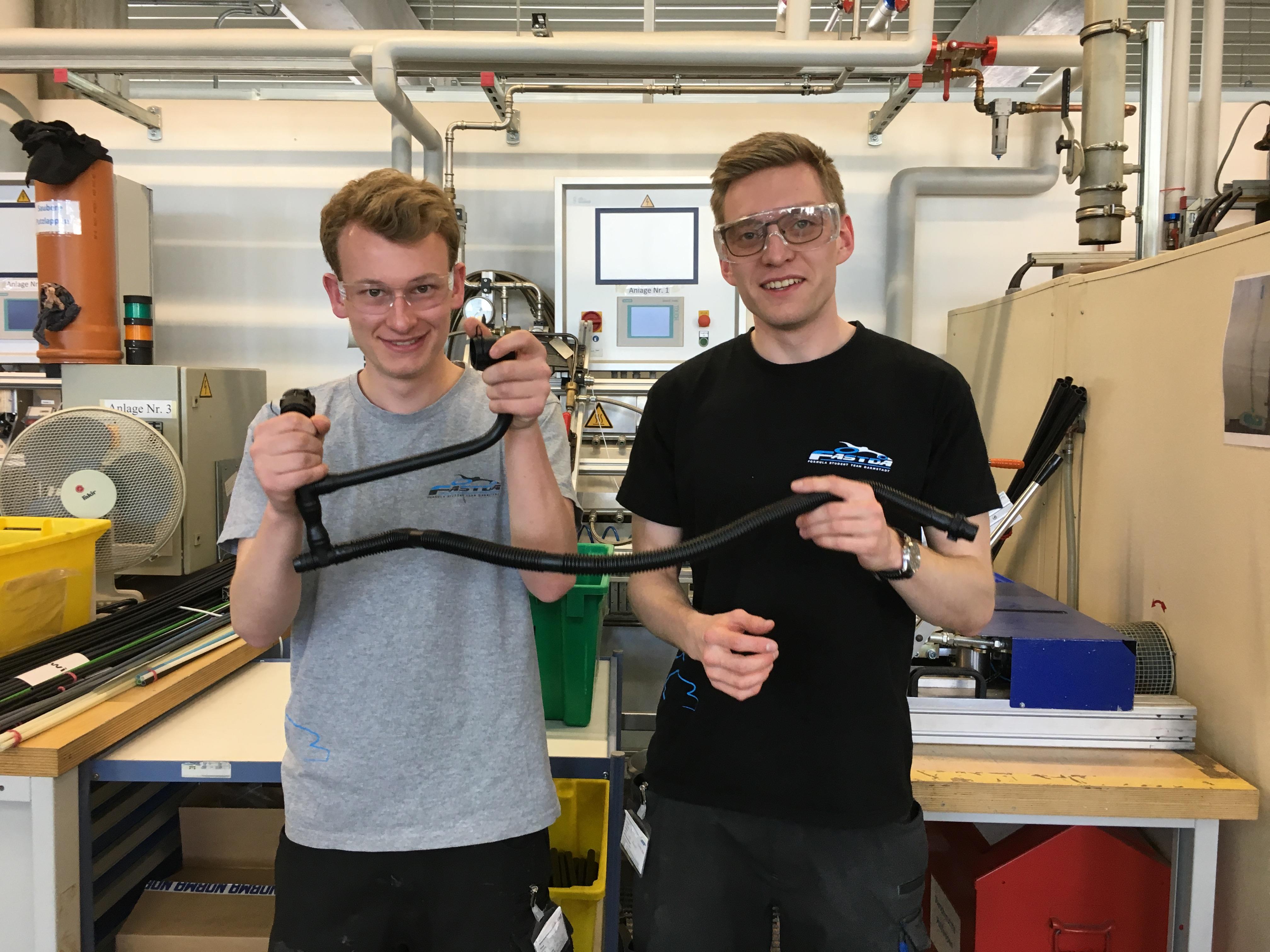 Sven Rühl und Lukas Koenen vom FaSTDa-Team 2019 in der Prototypenwerkstatt der NORMA Group mit einem Teil des Kühlleitungssystems